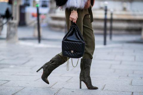 Trendfarben im Winter: Frau mit olivgrünen Stiefeln und einer Chaneltasche