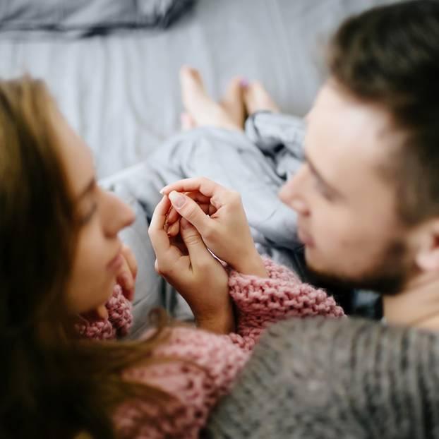 Manhattan-Effekt: Pärchen sitzt im Bett, hält Händchen und schaut sich in die Augen