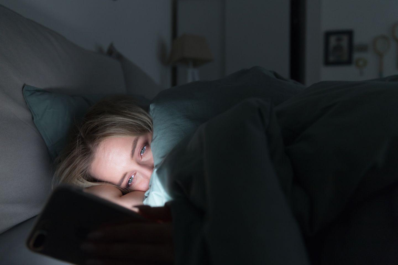 Kinder überwachen: Frau schaut im dunkeln unter Decker auf ihr Hnady