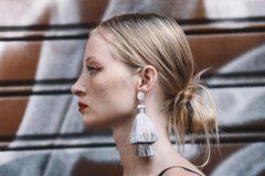Dutt-Frisuren: Frau mit tiefsitzendem Dutt und Statement-Ohrringen