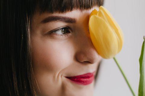 Bin ich lesbisch? Eine junge Frau mit Tulpe in der Hand
