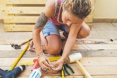 DIY Möbel: Ideen für Anfänger und Fortgeschrittene: Frau sitzt auf dem Boden und hantiert mit Werkzeug