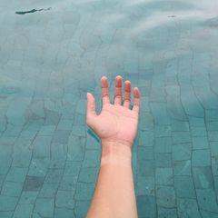 Floating: Eine Hand treibt auf der Wasseroberfläche