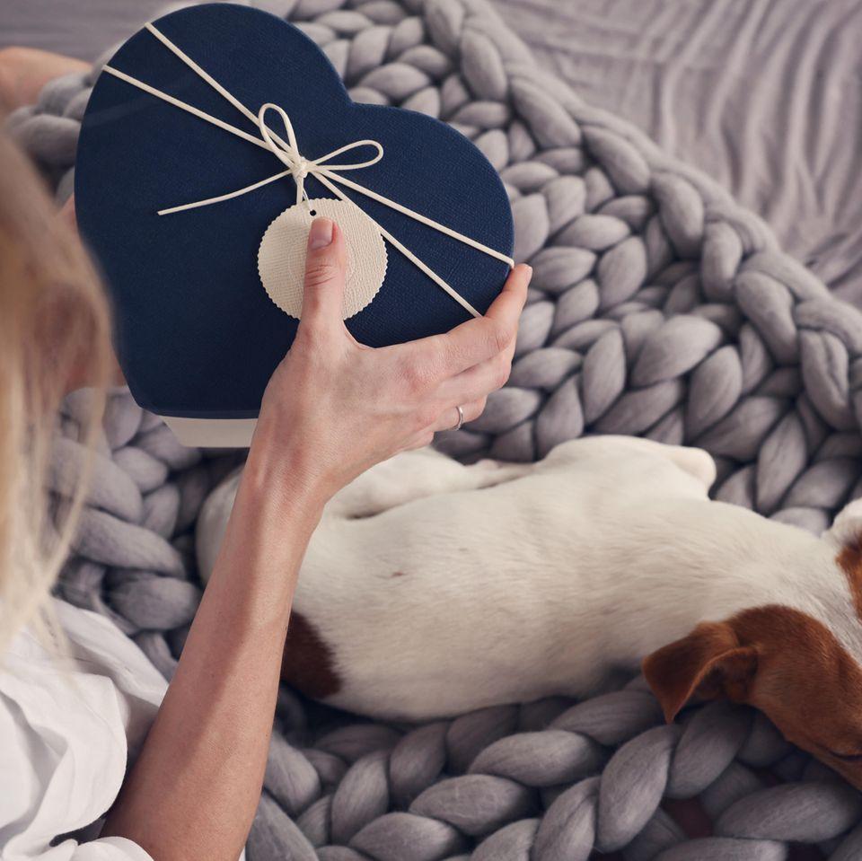 Geschenke für Hundebesitzer: Frau hat ein Geschenk für den Hund