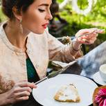Masturdating: Eine junge Frau beim Date mit Kuchen und Blumen auf dem Tisch