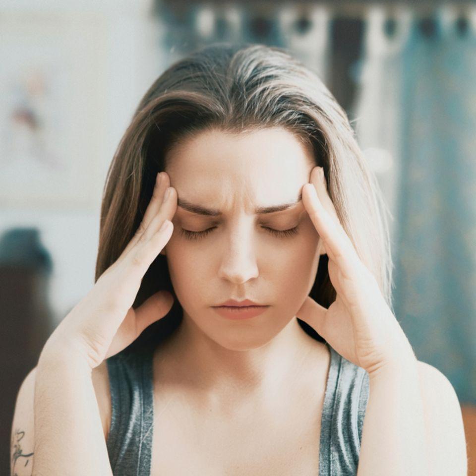 Kristalle im Ohr - Das hilft bei Drehschwindel: Frau fasst sich mit beiden Händen an die Schläfen