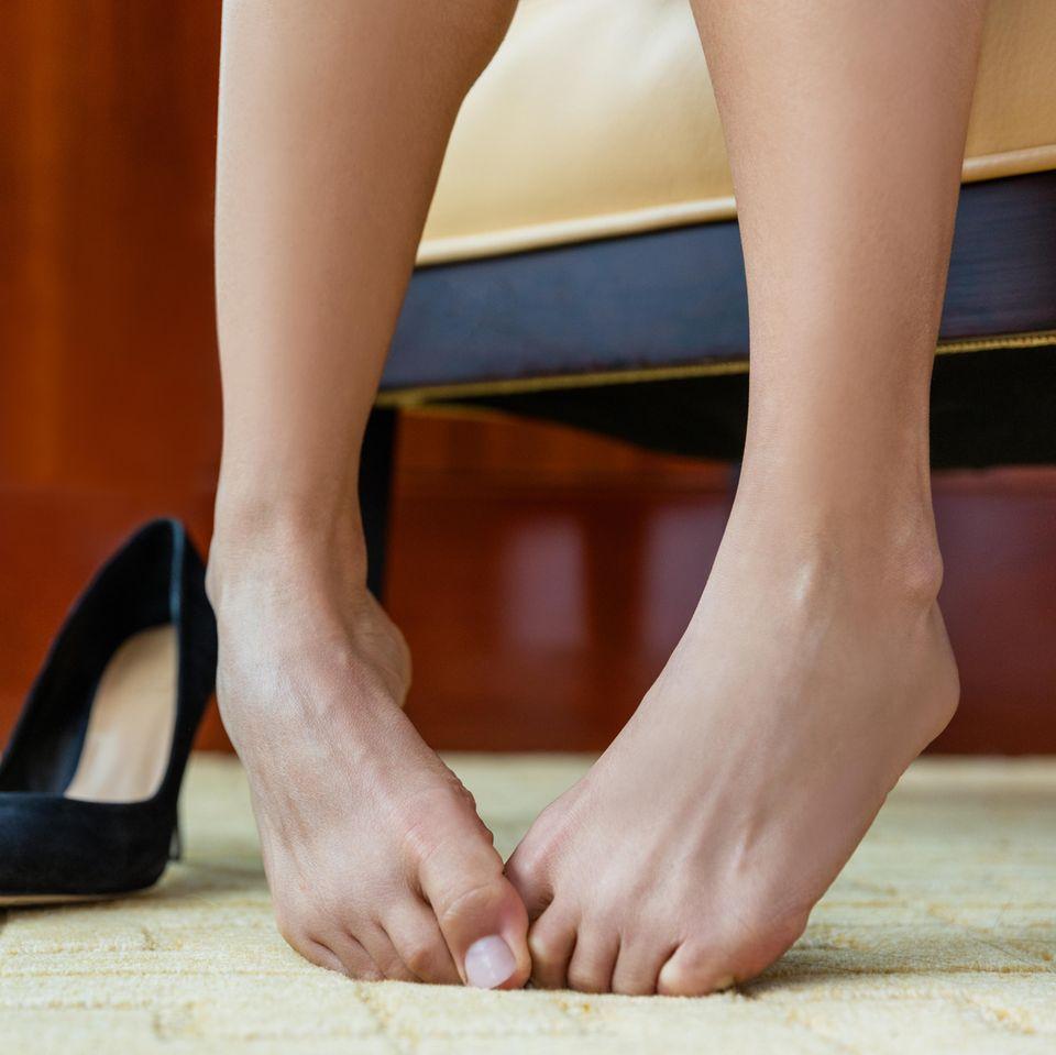 Fußgeruch: Zwei nackte Füße und Schuhe im Hintergrund