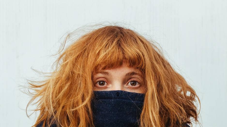 Anzeichen, dass du dich selbst nicht liebst: Eine junge Frau versteckt sich unter ihrem Pulli
