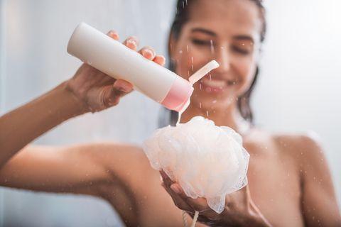 Duschgel selber machen - mit nur drei Zutaten! Frau steht in der Dusche und gibt Duschgel auf einen Schwamm