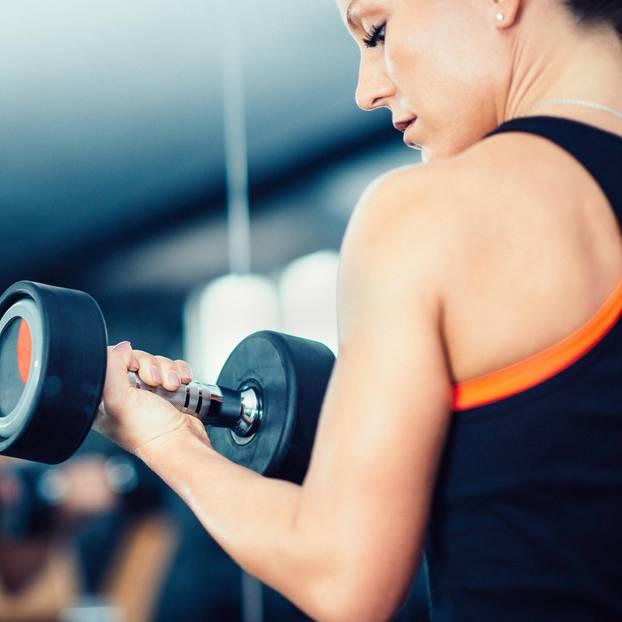 Gewichte stemmen: Frau trainiert mit Hanteln