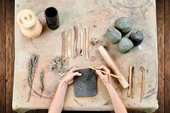 Töpfern: Ideen für selbst gemachte Keramik: Tonkugeln, Schaber auf dem Tisch. Hände verzieren Ton