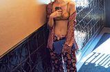 Lingerie: Frau in BH und Pyjama Hose an Wand gelehnt