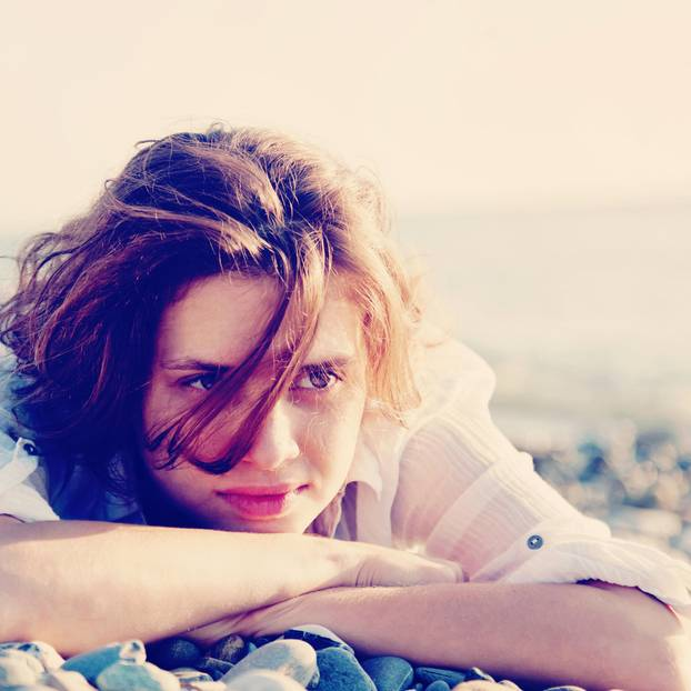 Gefühle verstehen: Eine Frau liegt an einem Kieselsteinstrand und denkt nach
