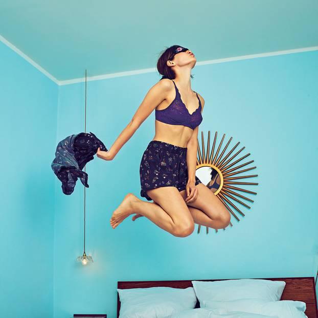 Lingerie: Frau in Unterwäsche hüpft auf Bett