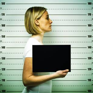 Verbrecherische Frauen: Eine Frau posiert für Polizeifoto