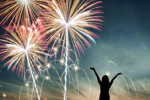 Silvesterwünsche für Familie, Freunde und Kollegen: Frau beobachtet Feuerwerk und streckt Arme in die Luft