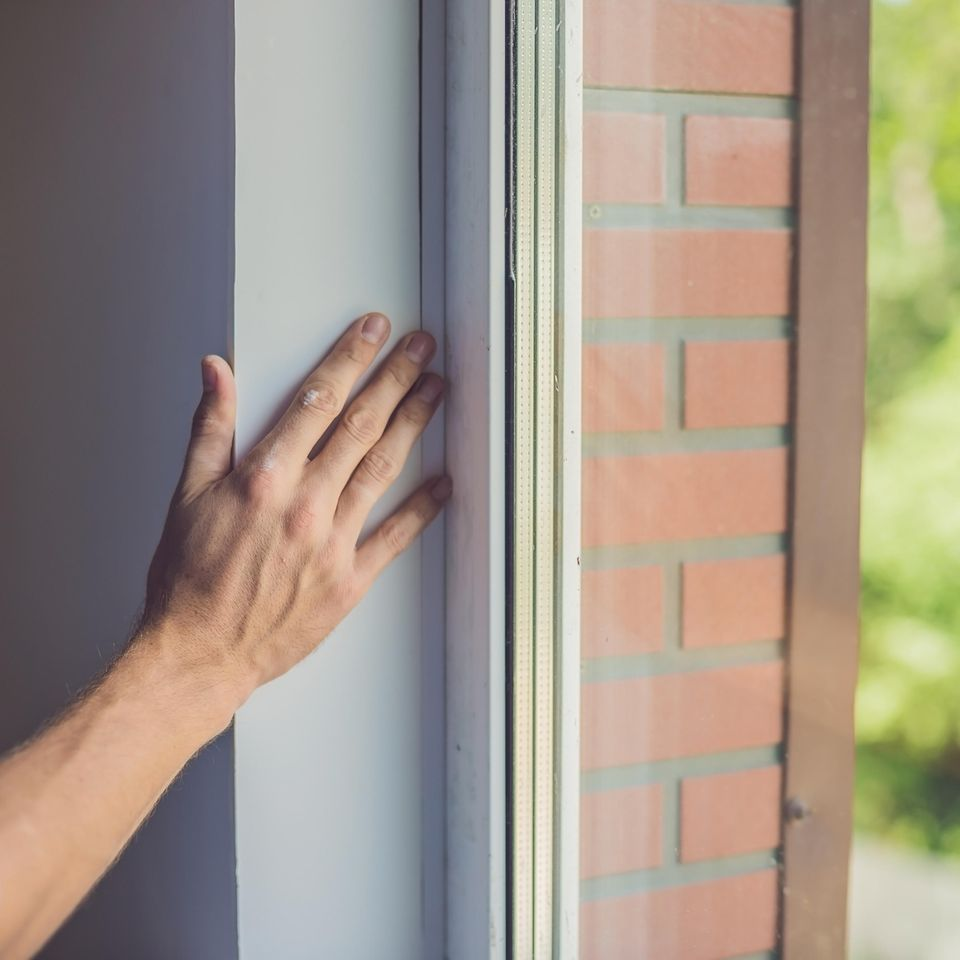 Fenster abdichten: Frau spürt Luftzug am Fenster