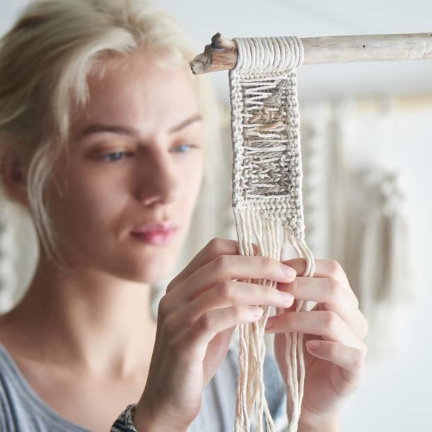 Makramee: Anleitung für Anfänger und DIY-Ideen: Frau knüpft einen kleinen Wandteppich