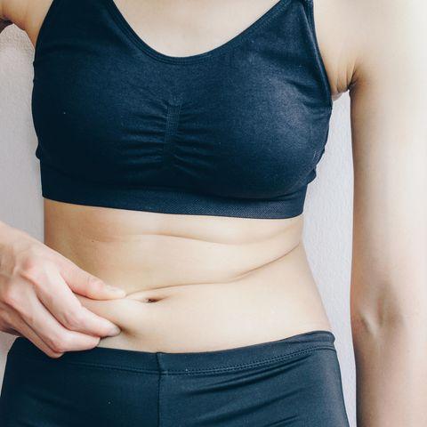 Fettverbrennung: Frau kneift sich in den Bauch