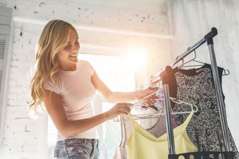 Bügel: Frau an Kleiderstange