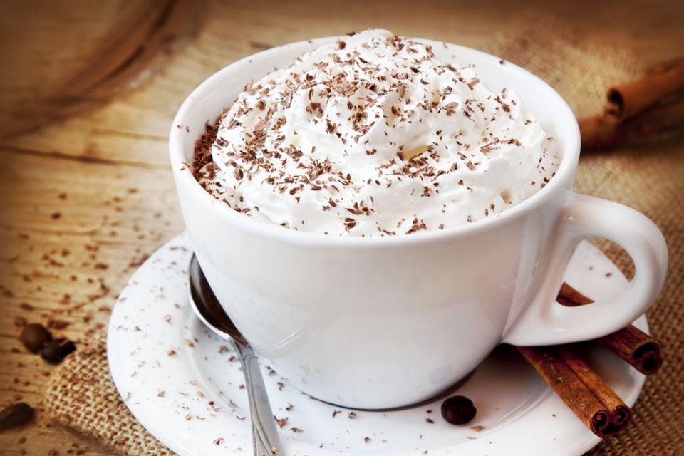 Weihnachtskaffee: So leicht geht das leckere Wintergetränk: Tasse gefüllt mit Kaffee und Sahnehaube, daneben Zimtstangen