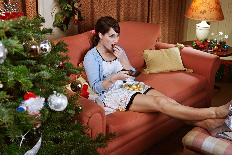 Weihnachtsfilme: Frau auf Sofa fernsehend