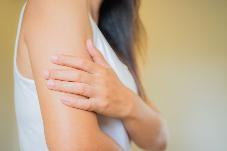 Muskelzucken: Das steckt dahinter: Frau fasst sich mit einer Hand an den Oberarm