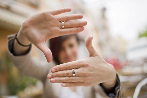 Frau schaut durch Hände