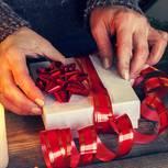 Weihnachtsgeschenke für die Mutter: Frau hält Geschenk in den Händen