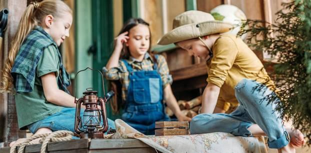 Schatzsuche: Kindergeburtstag richtig planen: drei Kinder sitzen über einer Weltkarte