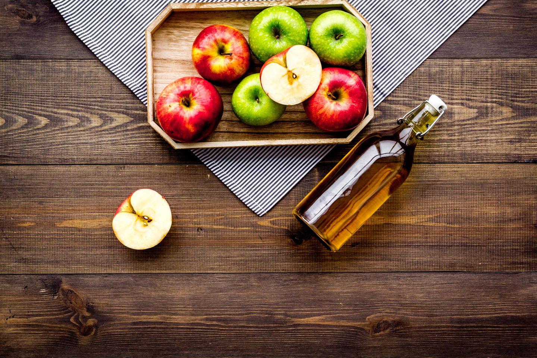 Apfelessig Haare: Tablett mit Äpfeln auf dem Tisch und einer Flasche Apfelessig