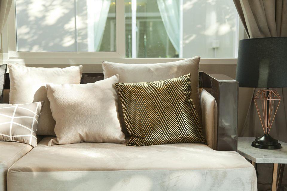 Wohnung teurer wirken lassen: goldenes Seidenkissen auf schlichter Couch
