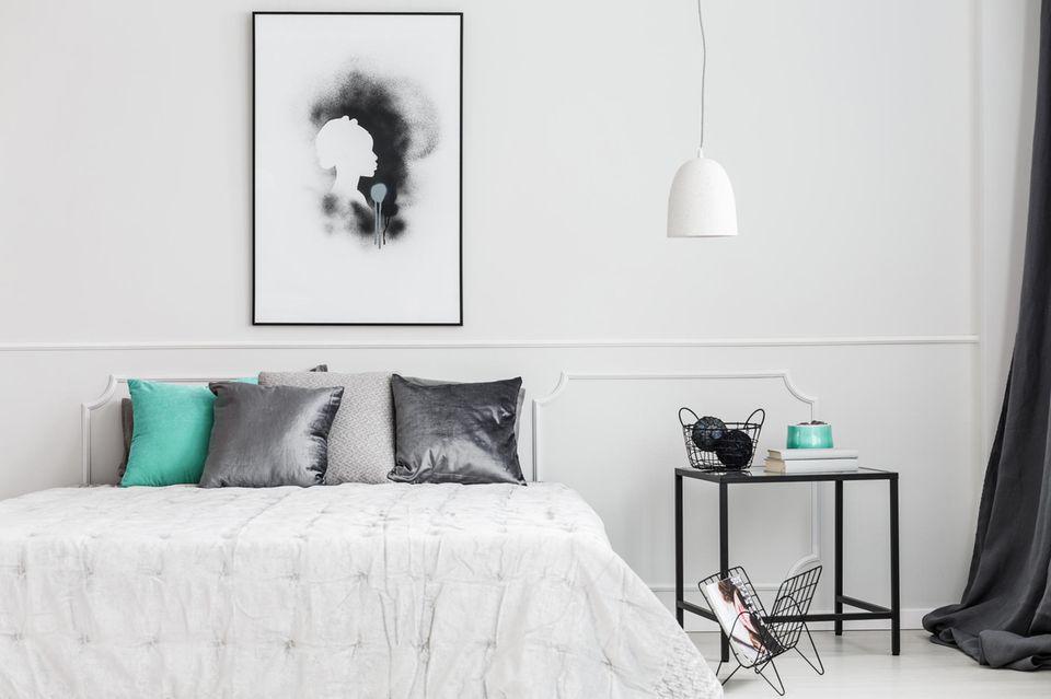 Wohnung teurer wirken lassen: Großes Bild hängt über weißem Bett