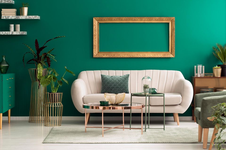 Wohnung teurer wirken lassen: Weiße Couch, smaragdgrüne Wand, Dekoelemente