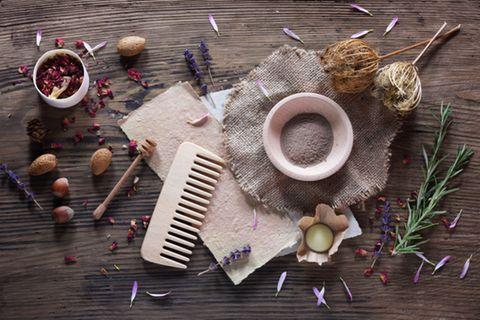Shampoo selber machen - Rezepte und Anleitung: Kamm, Schüssel mit Pulver und Rosmarinzweige liegen auf einem Holztisch