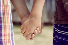 Gericht entzieht zwei Kindern ihren Nachnamen: Kinder halten Händchen