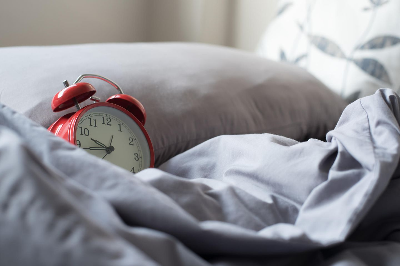 Früh aufstehen: Wecker auf dem Bett
