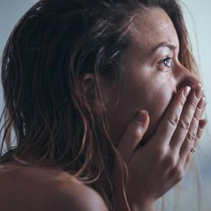 5 Phasen der Trauer: Frau schlägt Hände vor das Gesicht