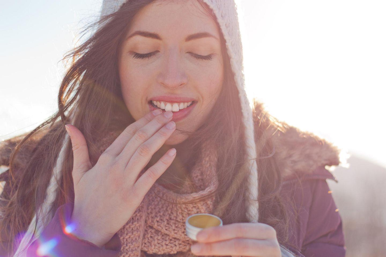 Brennende Lippen: Frau trägt Pflege auf Lippen auf
