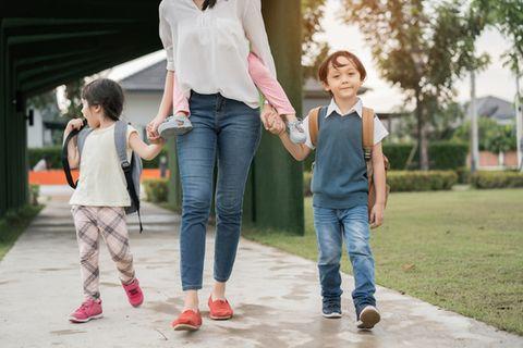 Rollenklischees: Mutter ist mit drei kleinen Kindern unterwegs