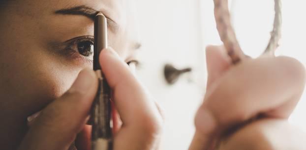 Bleached Brows: Frau, die sich die Augenbrauen anmalt