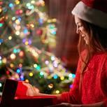 Geschenke für mich selbst: Frau öffnet Geschenk am Weihnachtsbaum