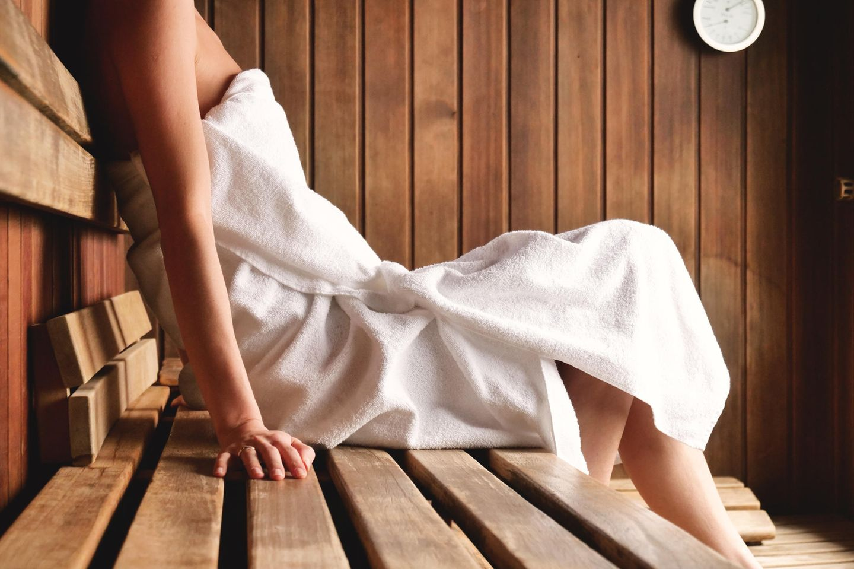 Sauna bei Erkältung: Ist das wirklich gesund? Frau sitzt in der Saune mit umgewickeltem Handtuch