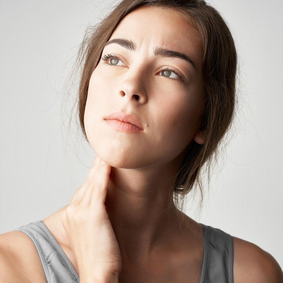 Hashimoto Thyreoiditis: Frau fasst sich an den Hals