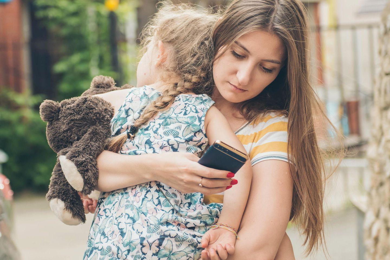 Freizeitplanung fürs Kind: Frau trägt Kind im Arm und schreibt am Smartphone