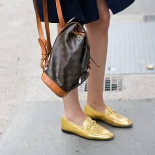 Festliche Schuhe ohne Absatz: Frau trägt Goldene Loafer