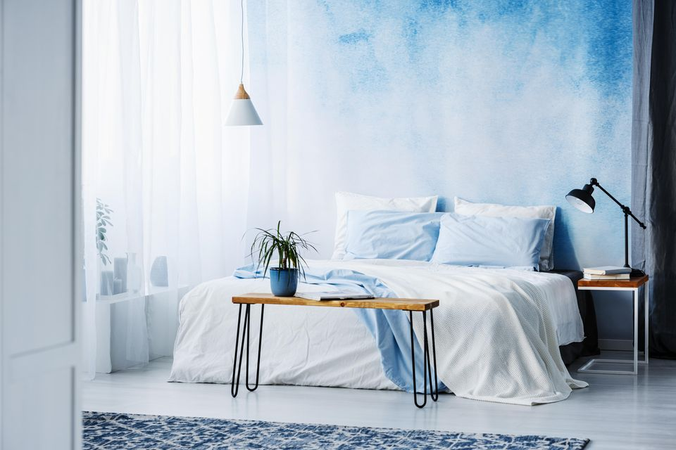 Schlafzimmer gemütlicher machen: blaue Stoffwand hinter dem Bett