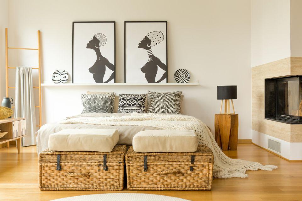 Schlafzimmer gemütlicher machen: Zwei Bast-Truhen am Füßendedes Bettes