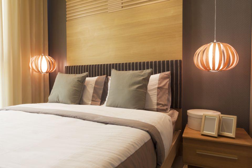 Schlafzimmer gemütlicher machen: Bett mit warmem Licht beleuchtet