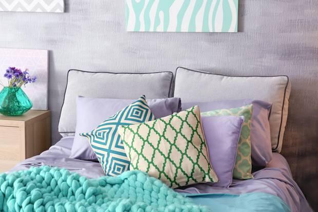 Schlafzimmer gemütlicher machen: Bett mit violetten und türkisen Decken und Kissen